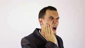 Hombre de negocios joven con un dolor de muelas, dolor de diente almacen de video
