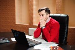 Hombre de negocios joven con un problema en la oficina que se sienta en su escritorio que frunce el ceño en su pantalla de ordena imagen de archivo