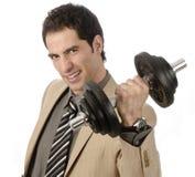 Hombre de negocios joven con una pesa de gimnasia Imagen de archivo