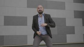 Hombre de negocios joven confiado que celebra el baile del éxito o del logro y que se divierte al aire libre delante del edificio metrajes
