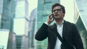 Hombre de negocios joven confiado que habla en su teléfono en la ciudad de Moscú, verano