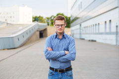 Hombre de negocios joven confiado que le mira con sus brazos cruzados imagen de archivo libre de regalías