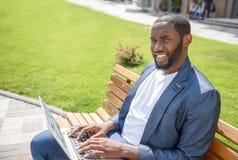 Hombre de negocios joven confiado que mecanografía en el ordenador Fotografía de archivo
