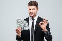 Hombre de negocios joven confiado que sostiene el dinero y que muestra la muestra aceptable Imagenes de archivo