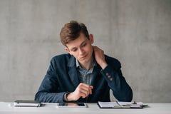 Hombre de negocios joven confuso de la rutina de la oficina foto de archivo