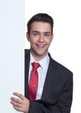 Hombre de negocios joven de risa detrás de un tablero blanco Imagenes de archivo