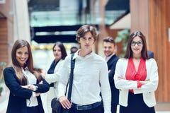 Hombre de negocios joven de Smilling en frente que su equipo blured en fondo fotografía de archivo libre de regalías