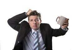 Hombre de negocios joven del adicto en traje y lazo que sostiene la taza de café vacía ansiosa Foto de archivo