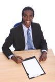 Hombre de negocios joven del afroamericano en el escritorio de oficina Foto de archivo