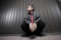 Hombre de negocios joven del muchacho que se pone en cuclillas Imágenes de archivo libres de regalías