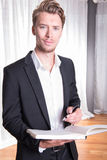 Hombre de negocios joven del retrato en el traje que toma notas en el libro Foto de archivo libre de regalías