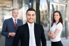 Hombre de negocios joven delante de un grupo de hombres de negocios al aire libre Fotografía de archivo