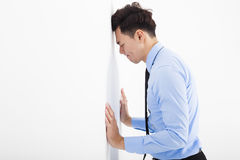 Hombre de negocios joven deprimido que se inclina en la pared en oficina Foto de archivo libre de regalías