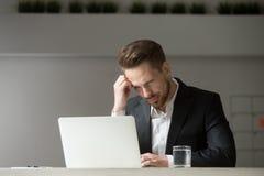Hombre de negocios joven desconcertado que mira la pantalla del ordenador portátil el lugar de trabajo Fotos de archivo