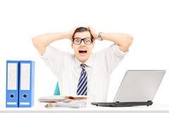 Hombre de negocios joven desesperado que grita en su oficina Imagen de archivo