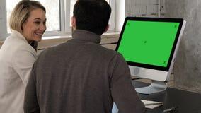 Hombre de negocios joven dos que tiene una reunión en la oficina que mira en monitor Exhibición verde de la maqueta de la pantall almacen de metraje de vídeo