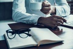 Hombre de negocios joven Drink Coffee y ordenador portátil con Imagen de archivo libre de regalías