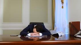 Hombre de negocios joven durmiente despertado por llamada de teléfono foto de archivo libre de regalías