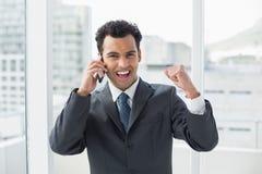 Hombre de negocios joven elegante alegre usando el teléfono móvil en oficina Imagen de archivo libre de regalías