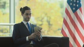 Hombre de negocios joven elegante con los dólares cerca de la bandera americana almacen de video