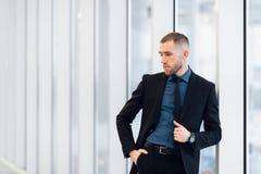 Hombre de negocios joven elegante que lleva un traje moderno, que es un alto cumplidor, coloc?ndose en el ?ltimo piso de un edifi foto de archivo libre de regalías