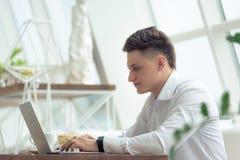 Hombre de negocios joven elegante que mira el ordenador portátil con sonrisa mientras que trabaja en proyecto en pequeño café aco fotografía de archivo libre de regalías