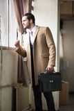 Hombre de negocios joven elegante que mira hacia fuera la ventana. fotografía de archivo libre de regalías