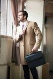 Hombre de negocios joven elegante que mira hacia fuera la ventana. foto de archivo libre de regalías