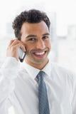 Hombre de negocios joven elegante sonriente usando el teléfono móvil Foto de archivo
