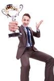 Hombre de negocios joven emocionado que gana un trofeo agradable Imagenes de archivo