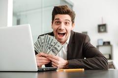 Hombre de negocios joven emocionado que muestra el dinero usando el ordenador portátil Imagen de archivo libre de regalías