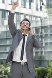Hombre de negocios joven emocionado usando el teléfono celular fuera de la oficina fotos de archivo