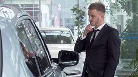 Hombre de negocios joven en coches de examen de un traje en venta en la representación almacen de metraje de vídeo