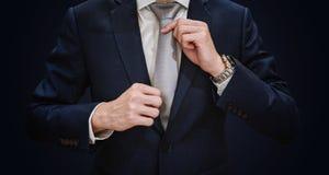 Hombre de negocios joven en corbata conmovedora del traje azul, en fondo azul marino foto de archivo