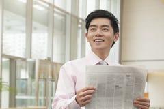 Hombre de negocios joven en del botón el periódico rosado de la lectura de la camisa abajo, Pekín, China Fotos de archivo