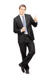 Hombre de negocios joven en el formalwear que se inclina contra la pared y el donante Foto de archivo