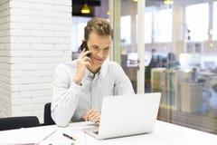 Hombre de negocios joven en el teléfono móvil en oficina Foto de archivo libre de regalías