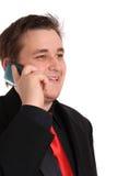 Hombre de negocios joven en hablar negro en el teléfono celular Foto de archivo libre de regalías