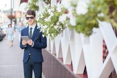 Hombre de negocios joven en la calle con la tableta foto de archivo libre de regalías