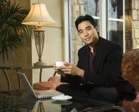 Hombre de negocios joven en la computadora portátil que sostiene una taza de café Fotografía de archivo libre de regalías