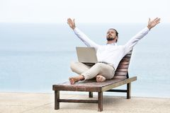 Hombre de negocios joven en la playa que descansa sobre su silla de cubierta usando su tableta fotos de archivo libres de regalías