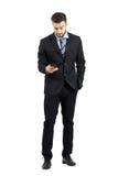 Hombre de negocios joven en mensaje de la lectura del traje en su teléfono móvil Imágenes de archivo libres de regalías