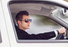 Hombre de negocios joven en su coche en la rueda Fotos de archivo