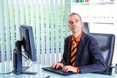 Hombre de negocios joven en su escritorio Fotos de archivo libres de regalías