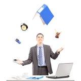 Hombre de negocios joven en un traje que hace juegos malabares con los materiales de oficina en el suyo Imagen de archivo