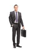 Hombre de negocios joven en un traje que sostiene una cartera Fotografía de archivo