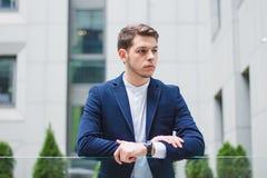 Hombre de negocios joven en una chaqueta azul En el reloj de la mano izquierda imagenes de archivo