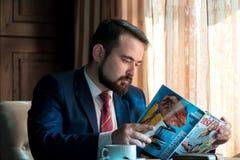 Hombre de negocios joven en una revista de la lectura del café Imágenes de archivo libres de regalías