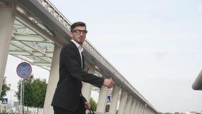 Hombre de negocios joven en vidrios y con la barba que corre a su aeroplano con la maleta grande en la cámara lenta Ciudad urbana metrajes