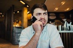 Hombre de negocios joven enojado que habla en el teléfono mientras que se sienta en un restaurante elegante Fotos de archivo libres de regalías